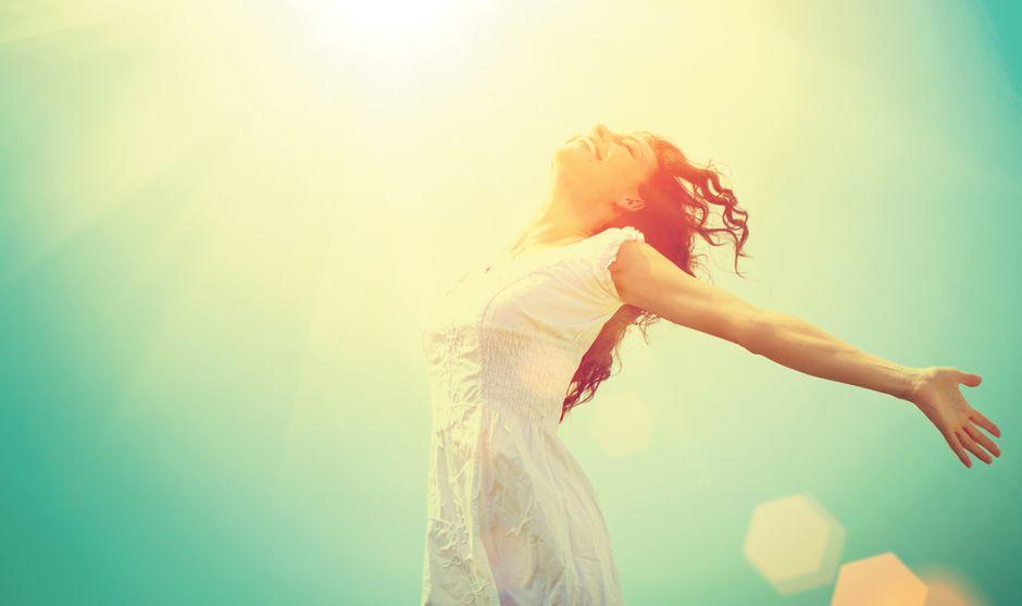 Femme en robe blanche qui danse et soleil