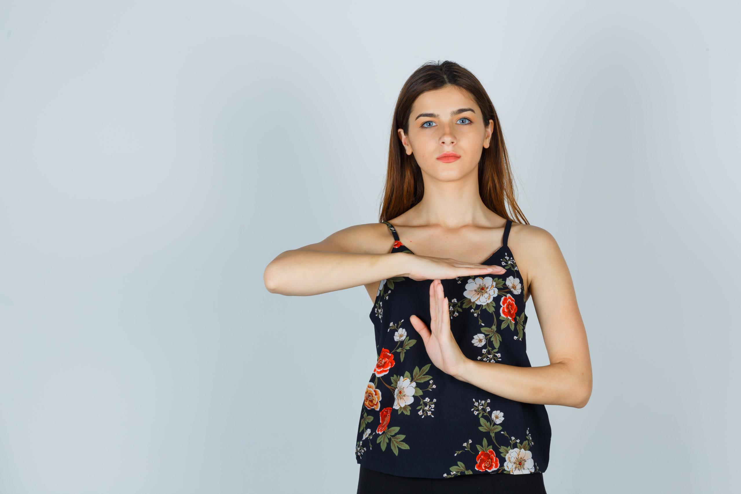 Jeune femme faisant geste pause avec ses mains